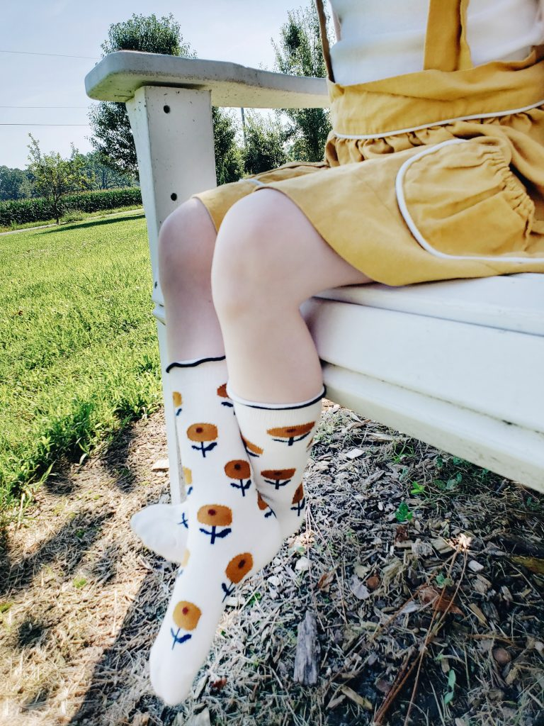 Young girl wearing small batch socks and a handmade skirt.